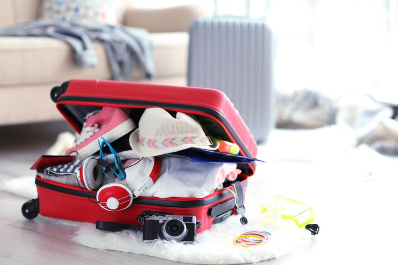 Собранный в спешке чемодан с неаккуратно сложенной одеждой предвещает череду неприятностей во время поездки.